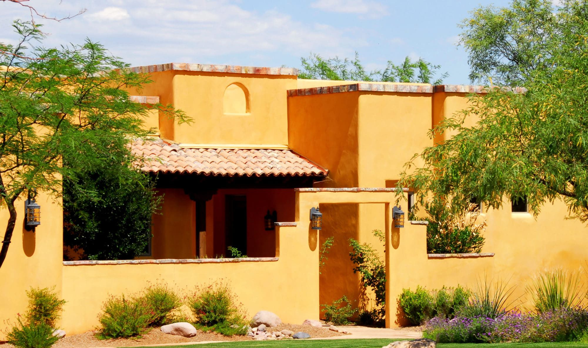 Look at the sunny glow on this new Arizona adobe style home with beautiful subtle southwestern stone accents all around the edges.
