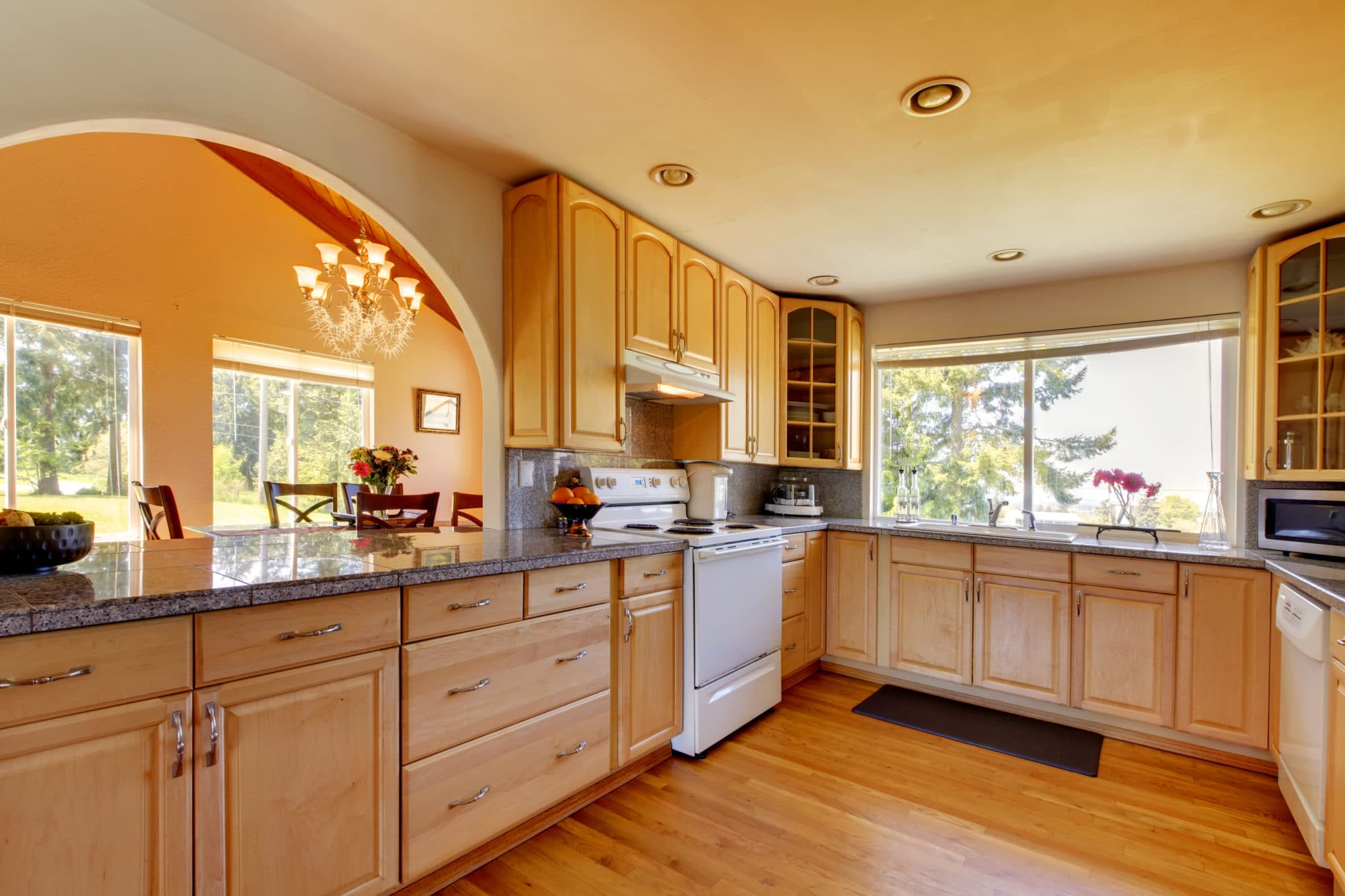 Notice the grand arched opening to the dining room from this sunny remodeled kitchen