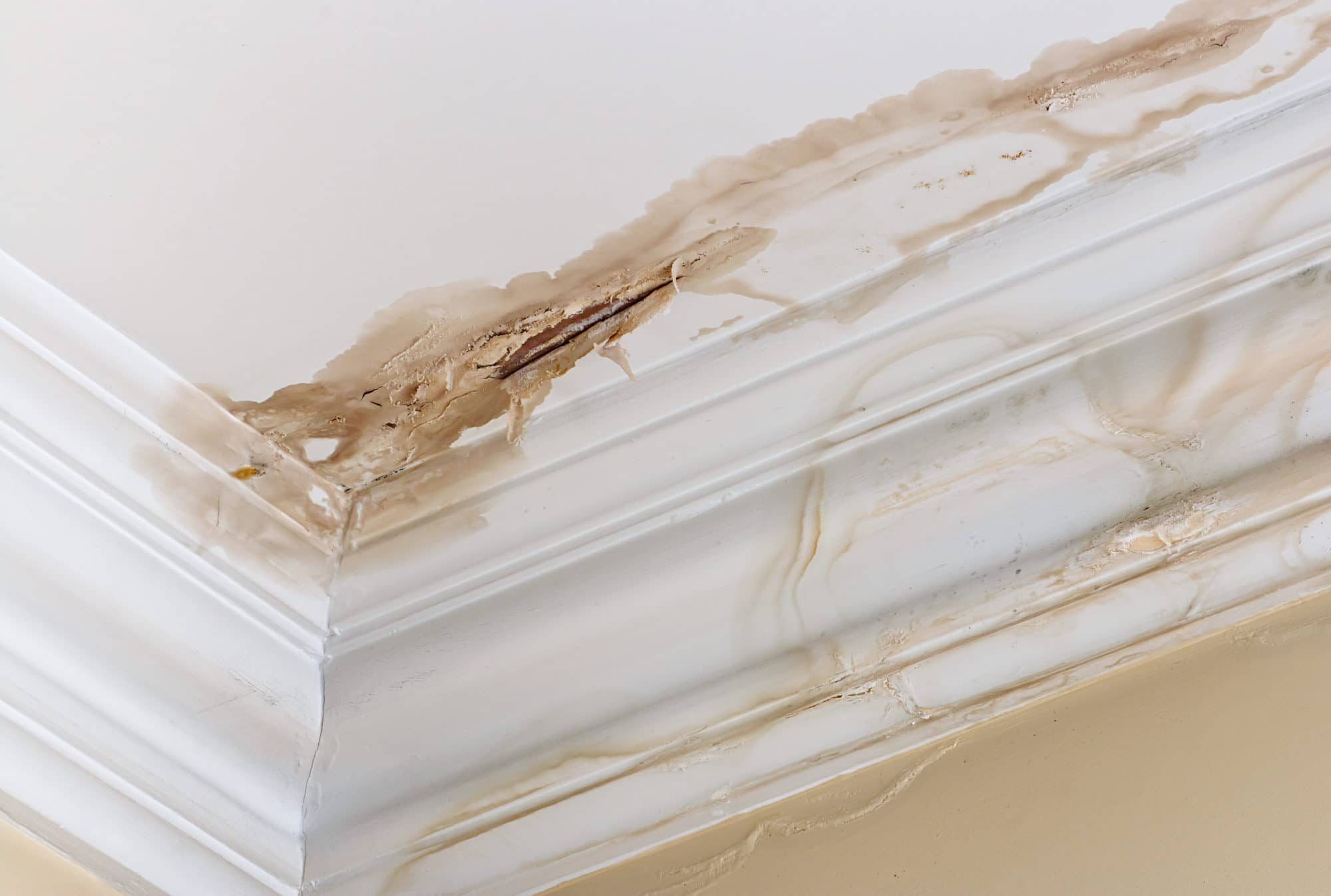 Peeling paint on an interior ceiling is a result of water damage caused by a leaking pipe dripping down from upstairs. It is a result of substandard plumbing completed by an unqualified plumber. A common home insurance claim.