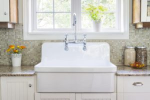 A beautiful kitchen faucet with a large rustic white porcelain farm sink and granite stone countertop on a sunny day. Sierra Remodeling is a Delta and Kohler faucets dealer.