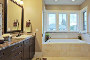 Luxury sunny bathroom with granite countertops, shaker cabinets, energy efficient windows and travertine flooring. Notice the matching tub and sink.
