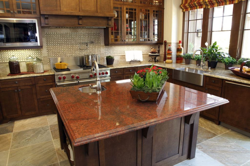A very unusual red granite island adorns this modern designer kitchen on top of beautiful slate brown tiles