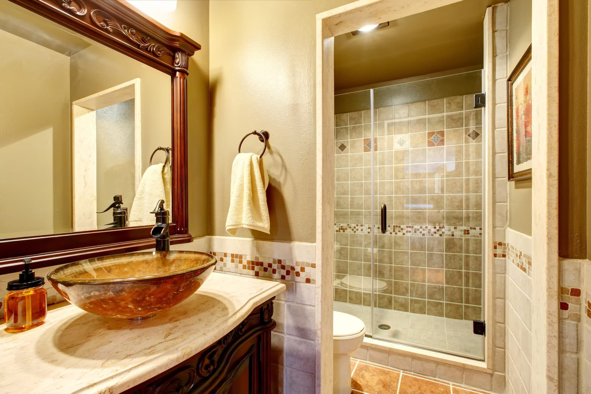 Rich bathroom vanity cabinet and matching mirrow with a gorgeous vessel sink. Well appointed and private adjacent shower and toilet room complete this nicely remodeled bathroom.