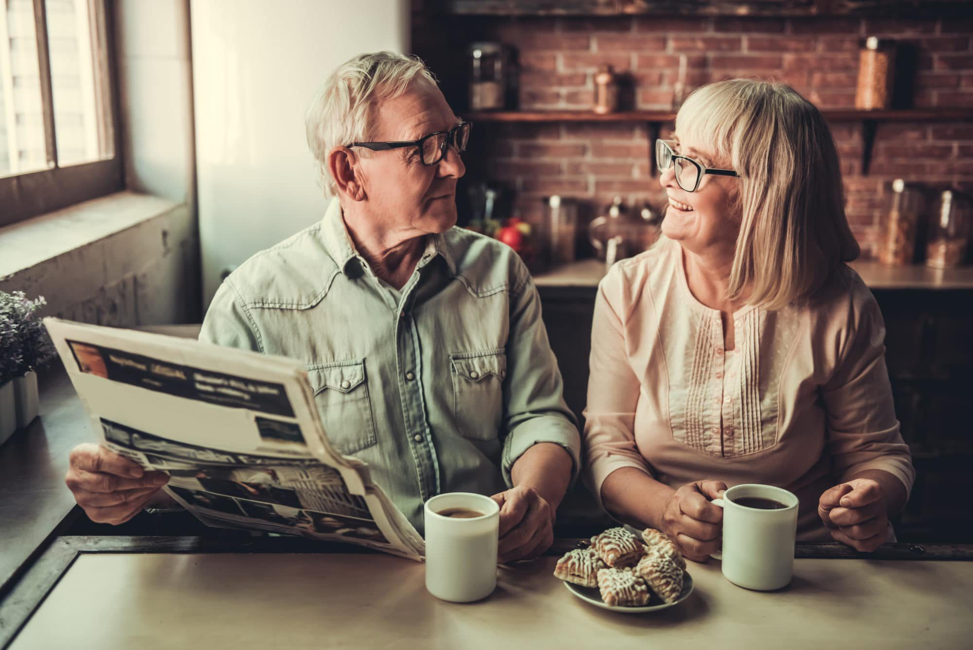 Home owners enjoying breakfast in their outdated kitchen reading their newspaper. Sierra Remodeling is in the news improving their community one home at a time!