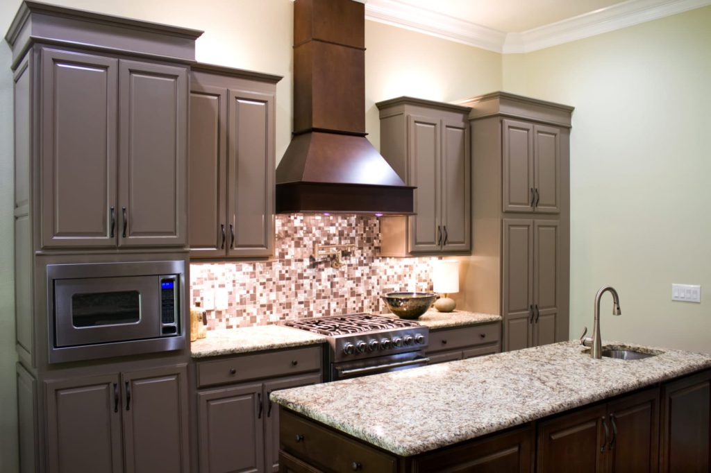 Cooking side of newly remodeled kitchen with granite countertops, striking cabinets, modern vent hood and six-burner gas stove and pot filler with large island. Sierra Remodeling loves to design your new kitchen!