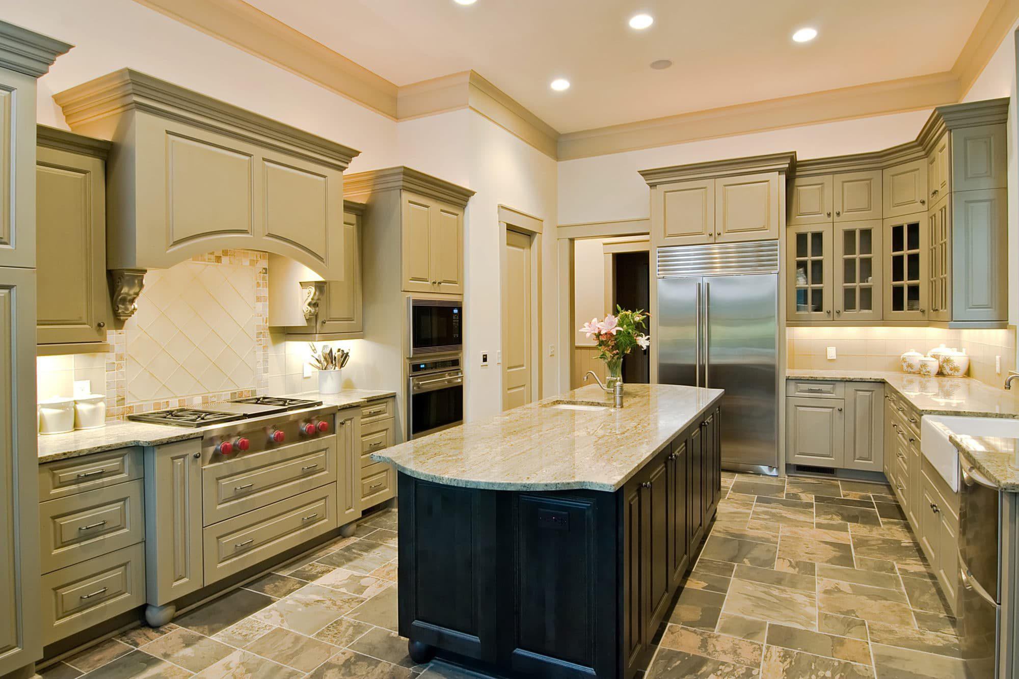 Green luxury kitchen with new cabinets, countertops, island, stainless appliances and geometrical slate floor