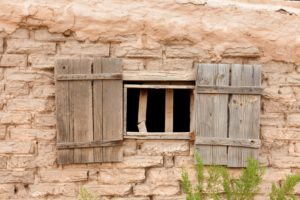Window opening with old wooden shutters in weathered mud brick wall near Tucson Arizona AZ