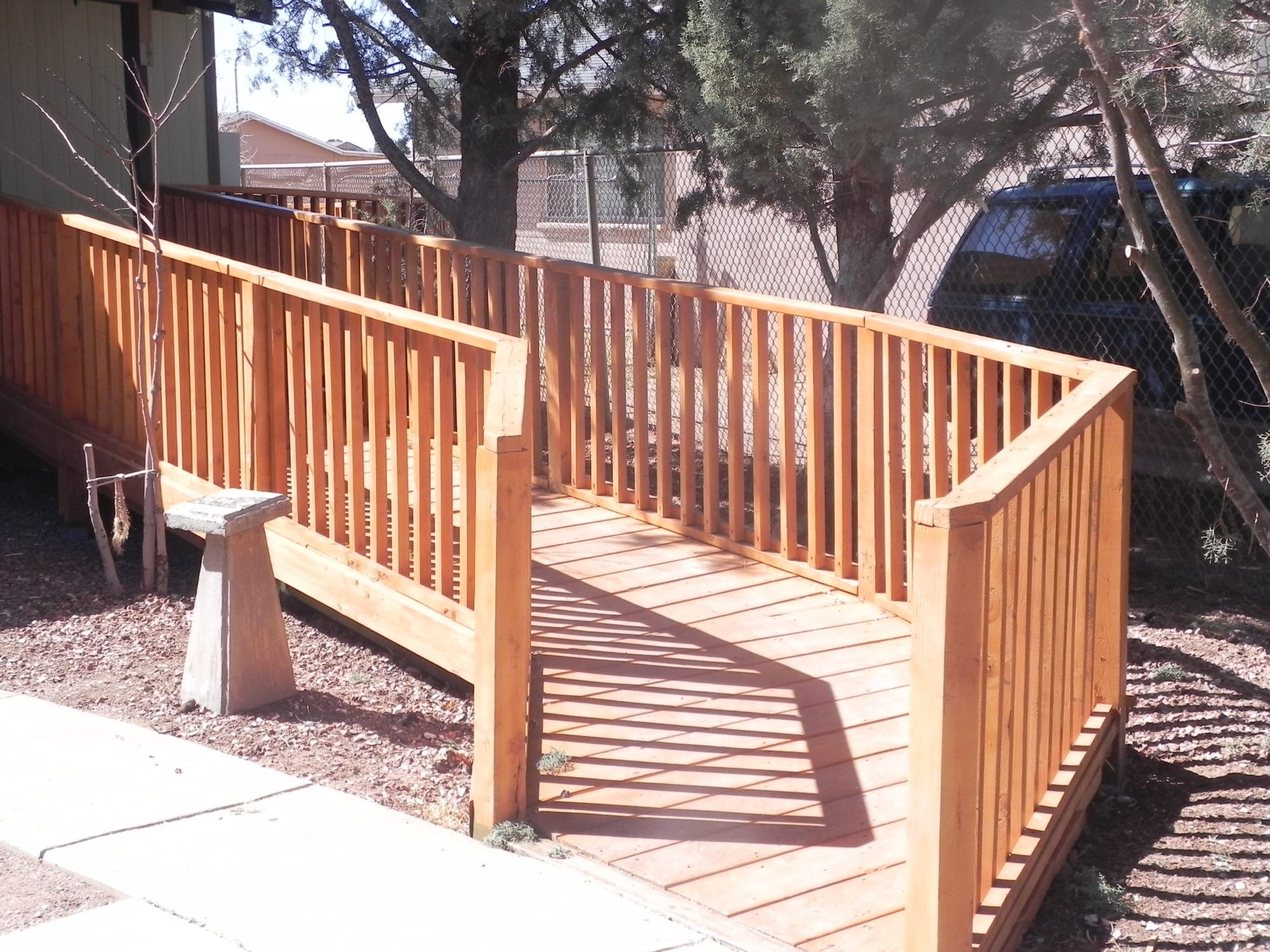 Sierra Remodeling - beautiful redwood wheelchair ramp with safety handrails and gentle turn